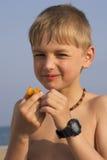 Junge auf dem Strand Pflaume essend Lizenzfreies Stockbild