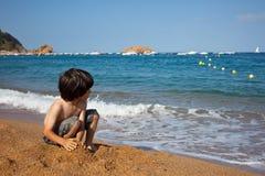 Junge auf dem Ufer von Meer Stockfotografie