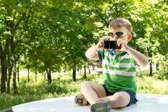 Junge auf die Oberseite eines Autos fotografierend mit einem Telefon Stockfotografie