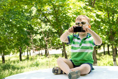 Junge auf die Oberseite eines Autos fotografierend mit einem Telefon Lizenzfreie Stockfotos