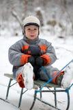 Junge auf einem alten Schlitten Lizenzfreie Stockfotografie