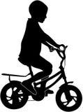 Junge auf einem Fahrradschattenbild Stockfoto