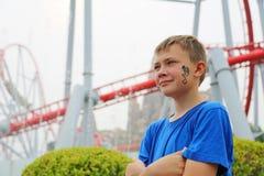 Junge auf einem Hintergrund der Achterbahn an einem Vergnügungspark Stockbilder