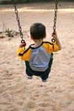Junge auf einem Schwingen am Park Stockfoto