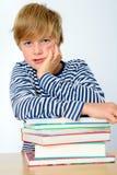 Junge auf einem Stapel von Büchern Stockfotos