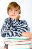 Junge auf einem Stapel von Büchern Lizenzfreie Stockfotografie