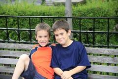 Junge auf einer Bank im Park Stockbilder