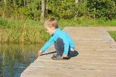 Junge auf einer Holzbrücke wird mit einem Stock im Wasser gespielt E Lizenzfreies Stockfoto
