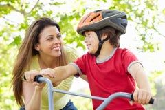 Junge auf Fahrrad mit Mutter Stockfoto
