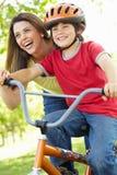 Junge auf Fahrrad mit Mutter stockbild