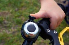 Junge auf Kindergelbem Fahrrad im Park, Steuer mit Bremsen und Hand mit Glocke stockbild