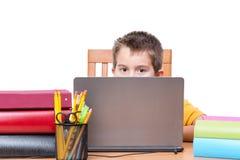 Junge auf Laptop studierend am Schreibtisch mit Büchern Lizenzfreie Stockfotos