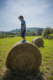 Junge auf rundem Heuballen Stockfotografie