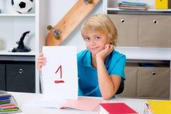 Junge auf Schreibtisch mit gutem Schulzeugnis Lizenzfreie Stockbilder