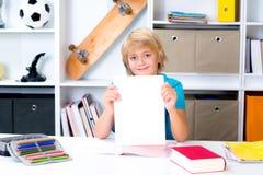 Junge auf Schreibtisch mit gutem Schulzeugnis Stockfoto