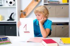 Junge auf Schreibtisch mit schlechtem Schulzeugnis Stockbild