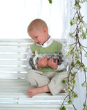 Junge auf Schwingen mit Häschen Lizenzfreies Stockfoto
