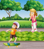 Junge auf Skateboard und Mutter im Park Stockfoto