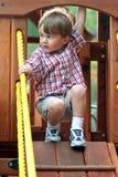 Junge auf Spielplatz-Ausrüstung Stockfoto
