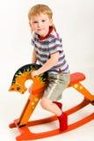 Junge auf Spielzeugpferd Stockbild