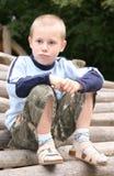 Junge auf Stapel der Protokolle Stockbild