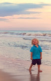 Junge auf Strand bei Sonnenuntergang Stockbild
