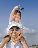 Junge auf Vaterschultern mit Spielzeugflugzeug Stockbilder