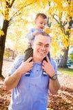 Junge auf Vati-Schultern Stockfoto