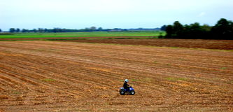 Junge auf Viererkabel durch den Bauernhof Stockfoto