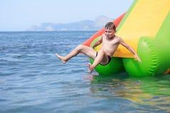 Junge auf Wasserrutschen stockbild
