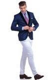 Junge aufknöpfende Jacke des Geschäftsmannes beim Gehen Stockfoto