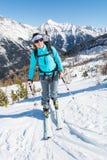 Junge aufsteigende Frau eine Steigung auf Skis Stockfotos