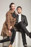 Junge aufwerfende Modepaare beim Sitzen Stockfoto