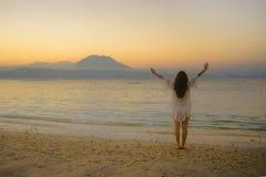 Junge ausgebreitete Arme der glücklichen und gesunden Frau, die frei auf dem Sandstrand betrachtet HorizontMeerwasser- und Vulkan stockfotos