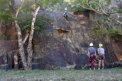 Junge australische Leute, die von einer Klippe in Brisbane Australien abseiling sind stockfoto