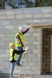 Junge Auszubildendfrau mit ihrem Tutor auf einem Bauwebsitebesuch, Baugewerbe lizenzfreies stockbild