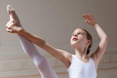 Junge Ballerina, die ihre Zehe hält Stockfotografie