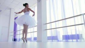 Junge Ballerina im weißen Ballettröckchen und pointes, die in Tanz in der Ballettklasse spinnen stock video footage