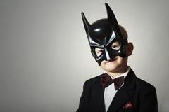 Junge in Batman-Maske. Lustiges Kind im schwarzen Anzug Stockfotos