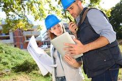 Junge Bauarbeiter, die an Standort arbeiten Lizenzfreie Stockbilder