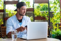 Junge beginnen oben Hübscher Geschäftsmann, der an der Laptop-Computer, Gebrauch Smartphone arbeitet Lizenzfreie Stockbilder