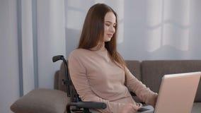 Junge behinderte Frau, die zu Hause mit Laptop arbeitet stock video