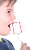 Junge beißt ein Geschenk auf einem Bolzen Lizenzfreies Stockfoto