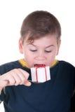 Junge beißt ein Geschenk auf einem Löffel Stockbilder
