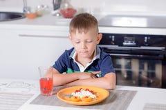 Junge bei Tisch, der Platte des Käses und der Frucht betrachtet Stockfoto