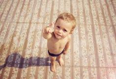 Junge beim Badebekleidungszeigen Stockfotos