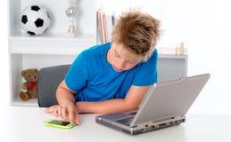 Junge benutzt Smartphone und Computer Stockbild