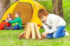Junge bereitet Feuer im Wald mit anderen Kindern vor Lizenzfreie Stockfotografie