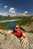 Junge Bergsteigerreichweiten für Griff in den Bergen lizenzfreies stockfoto