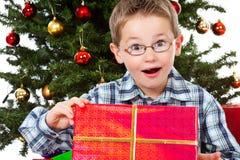 Junge überrascht vom Inhalt seines Weihnachtsgeschenks Lizenzfreie Stockfotos